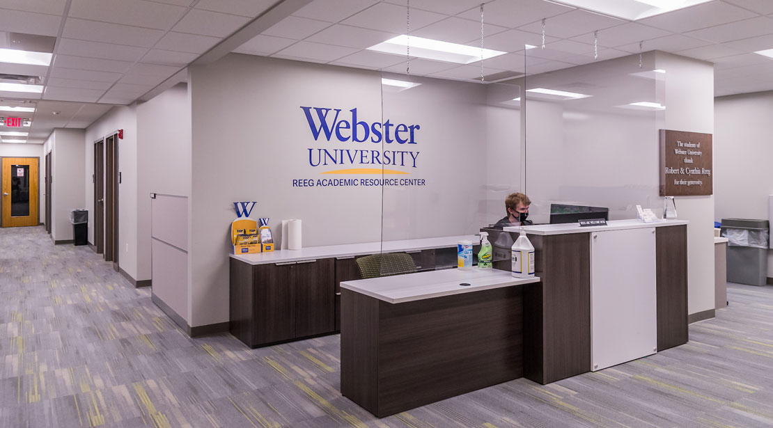 Welcome desk with a receptionist in the Reeg Academic Resource Center, with a hallway on either side.