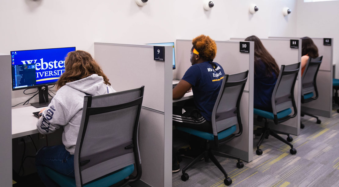 Four computer testing cubicles with computer monitors and dividers are in a row along the wall of the Reeg Academic Resource Center's testing center.  Each station has a camera on the wall above it, and a student occupies the wheeled chair in front of its monitor.