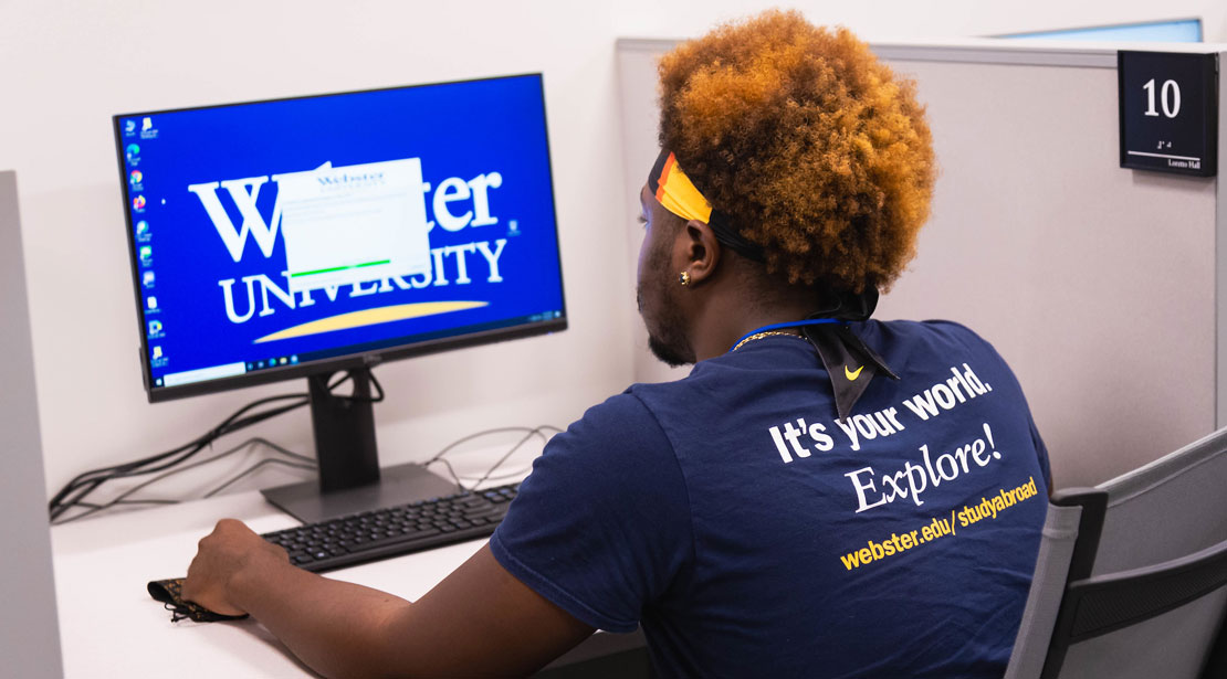 In the Reeg Academic Resource Center's testing site, a young dark-skinned male student with orange curly hair sits in front of a computer monitor.