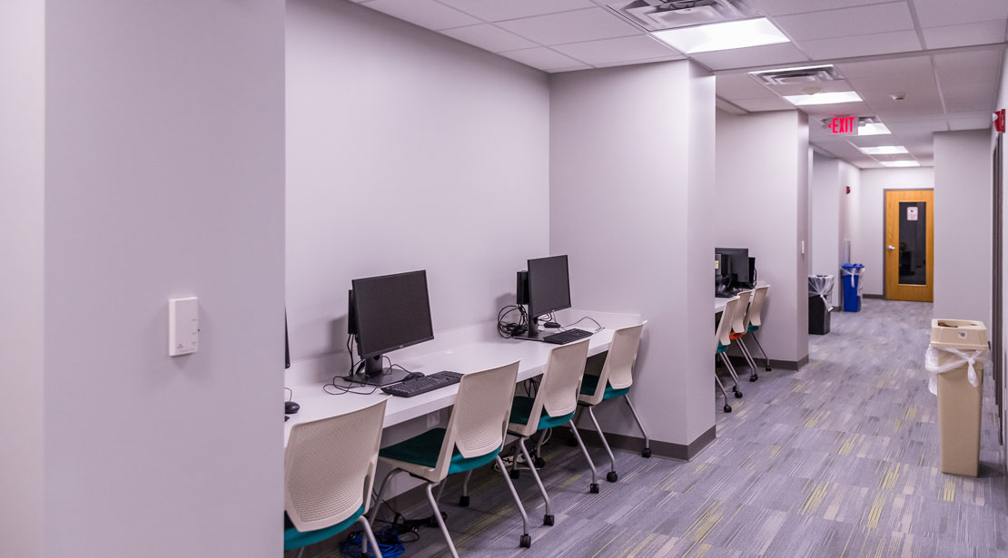 This is the hallway to the left of the welcome desk and shows a row of computer stations available for students.  There are chairs on wheels lining the long desks with computers.