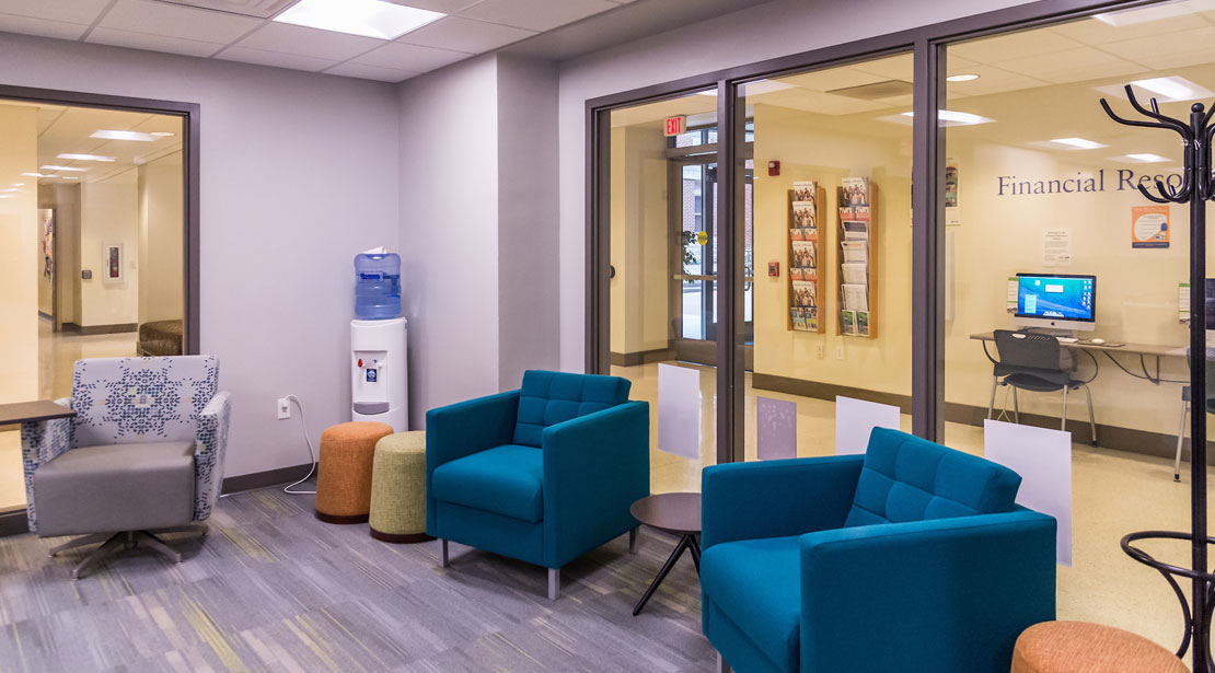 The lobby area of the Reeg Academic Resource Center has two comfortable turquoise chairs on the right side in front of a large window to the hallway, two small stools in yellow and orange in the middle in front of a water station, and one comfortable gray patterned chair with a side desk attached.