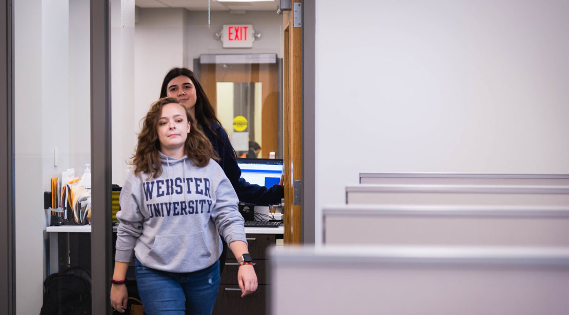 A young adult-aged female student wearing a gray Webster University sweatshirt walks into the Reeg Academic Resource Center's testing site in front of another woman with long black hair.