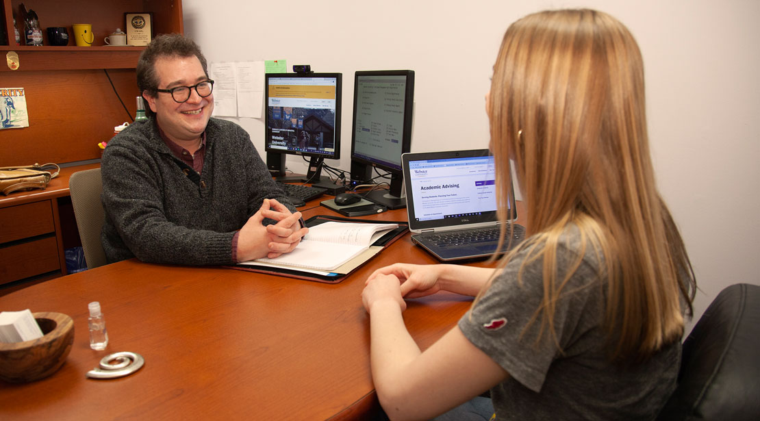 Academic advisor and student in conversation at a desk.