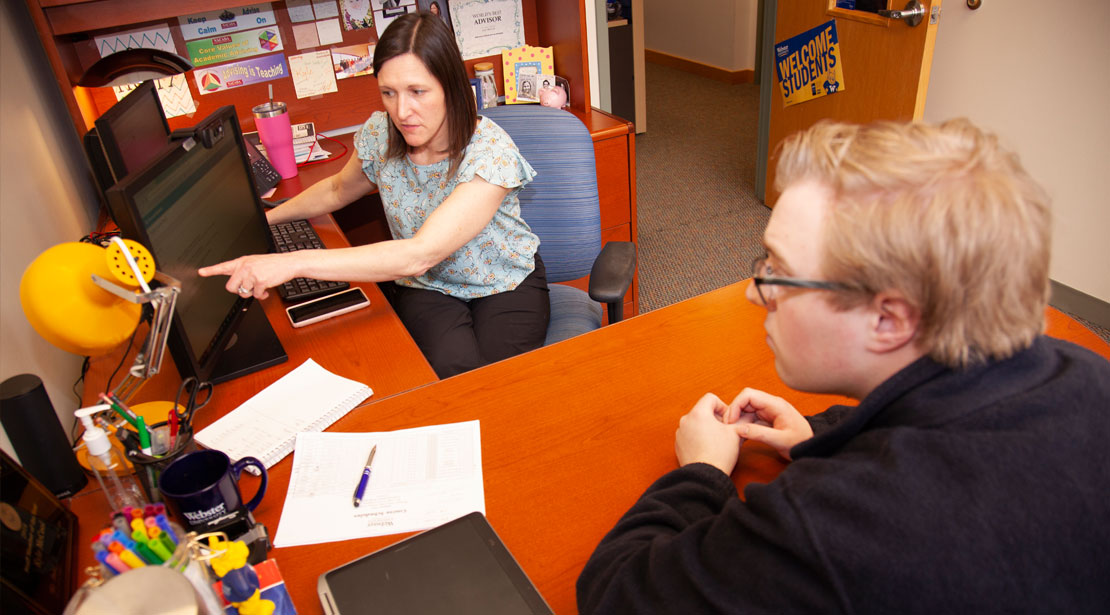 The academic advisor points to a computer screen while talking with a student during an advising session.