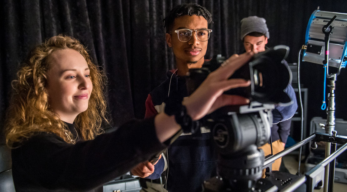 Two students working together learning to use video camera equipment.